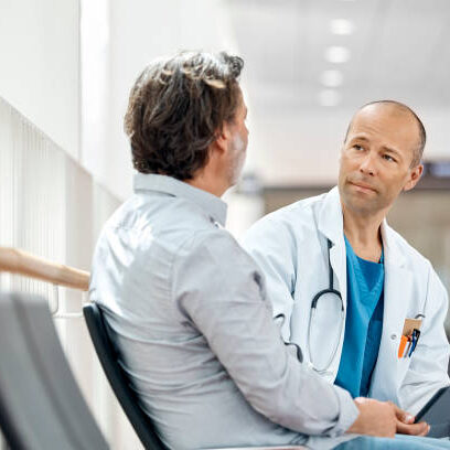 Male doctor counseling mature patient in waiting room. Medical professional is listening to ill man while holding digital tablet in hospital. They are sitting on seat.